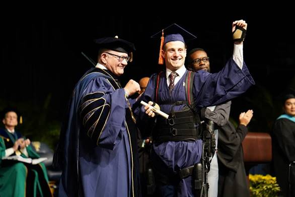 Aldo Amenta '18 crosses the commencement stage with the help of an exoskeleton